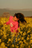 Girl picking flowers. Young girl in a field of yellow flowers Royalty Free Stock Photo