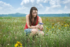 Girl picking flowers. Pretty young girl picking flowers in summer meadow Stock Image