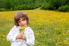 Girl picking flowers in yellow spring meadow. Beautiful scenic in Pyrenees spain Royalty Free Stock Image