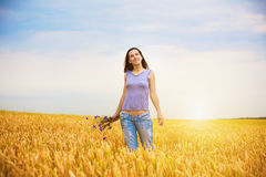 Girl is picking flowers on the yellow wheat field Stock Image