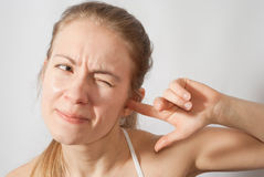 Girl picking her ear. Suffering from noise royalty free stock image