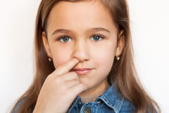 Girl Picking His Nose. Little Six Year Girl Picking His Nose On White Background, Looking At Camera Close-up Stock Images
