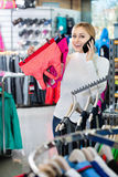 Girl picking a sport bra  while talking to the phone Stock Photos