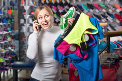 Girl picking a sport bra  while talking to the phone Royalty Free Stock Image