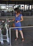 Girl picking up luggage trolley Stock Image