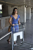 Girl picking up luggage trolley Stock Photography