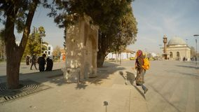 Girl is picking up water in the spring in the middle of the central street of the ancient city of Konya. KONYA / TURKEY - 11.20.2016 central streets of the stock video