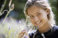 Girl (8-10) picking wildflowers in field, smiling, portrait Stock Photo