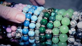 Girl picks in the market and trying beads and pendants. stock footage
