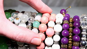Girl picks in the market and trying beads and pendants. Macro shot stock footage