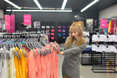 The girl picks a new dress in the store Royalty Free Stock Photography