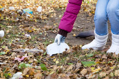 Girl picks up trash in the park. Girl fighting for the purity of by collecting garbage in park Stock Photo