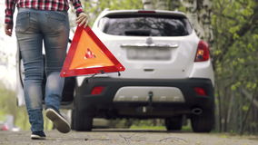 Girl picks up the warning triangle and drives away. Young girl 20s 30s cancels a call to rescue service and picks up the warning triangle with asphalt, sits in stock footage