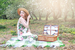 Girl on a picnic in the apple orchard with basket of products Royalty Free Stock Image