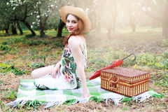 Girl on a picnic in the apple orchard with basket of products Stock Photos