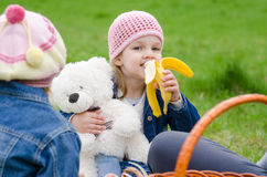 Girl on picnic eats a banana and holds bear Royalty Free Stock Images