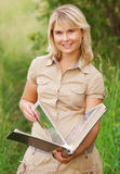 Girl with  picture album. The beautiful young woman holds a picture album in hands and smiles, against a summer landscape Stock Photography