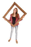 Girl in picture frame. A tall pretty woman holding a picture frame for her upper body, in jeans and a checkered shirt, over white royalty free stock photo
