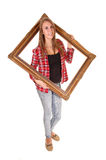 Girl in picture frame. A tall pretty woman holding a picture frame for her upper body, in jeans and a checkered shirt, over white royalty free stock image