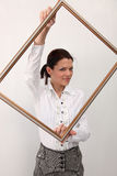 Girl with picture frame. Beautiful girl in white trousers and blouses holds picture  frame Stock Photography