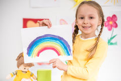 Girl with picture of rainbow. Little pretty smiling girl in yellow  pullover  holding a picture of rainbow on colorful background Stock Photos