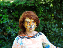 The girl with a picture of a tiger on the face. Red hair girl with a picture of a tiger on the face Stock Photography