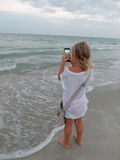 Girl pictures of the sea on the phone Stock Photography