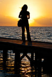 Girl on the pier. A girl observing the sunset from the pier in Marsala, Sicily Stock Images