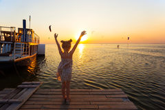 Girl at the pier. Girl on the pier in the background of the sea, ship and sunset. Ukrainian landscape Stock Photo