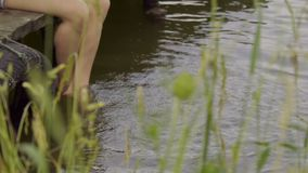 Girl on pier. Girl sitting on wooden pier and dangling her feet in the water stock video