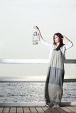 Girl on pier with kerosene lamp Royalty Free Stock Image