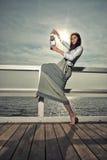 Girl on pier with kerosene lamp Stock Images