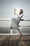 Girl on pier with kerosene lamp Royalty Free Stock Photo