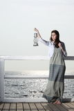 Girl on pier with kerosene lamp Stock Photo