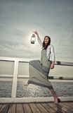 Girl on pier with kerosene lamp Stock Images