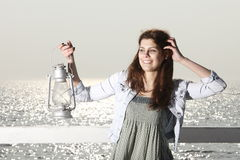 Girl on pier with kerosene lamp Stock Photos