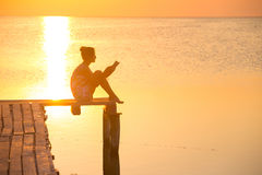 Girl at the pier. Girl reading a book on a pier in the background of the sea and sunset. Ukrainian landscape Royalty Free Stock Photography