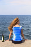 Girl on the pier. A girl sits on a pier with a bottle of wine royalty free stock images