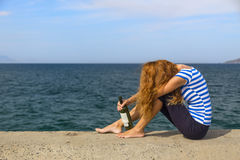 Girl on the pier. A girl sits on a pier with a bottle of wine stock photography