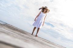 Girl on the pier. Girl walking on the wooden pier Royalty Free Stock Photo