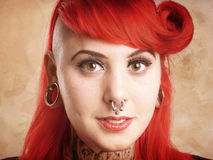 Girl with piercings and tattoos. Young alternative woman with side cut, facial piercings and tattoos - with added texture filter effect royalty free stock photography
