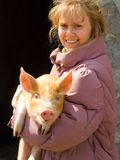 The girl and pig. The girl holds on hands of a red pig stock photography