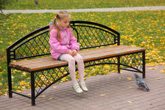 The girl and pigeon. The little girl sits on bench and looks at pigeon royalty free stock image