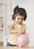 Girl With Piggy Bank. A young girl is playing with a piggy bank. She is looking away from the camera. Vertically framed shot stock photos