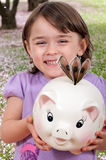 Girl with Piggy Bank. Cute little girl with dolar biils in piggy bank with a cherry blossom background royalty free stock photos