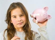 Girl piggy bank. Girl shaking a piggy bank Royalty Free Stock Photo