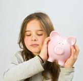 Girl piggy bank. Girl shaking a piggy bank Stock Photo