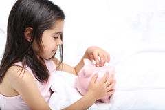 Girl with piggy bank. Beautiful little girl with piggy bank on white bed Royalty Free Stock Photography