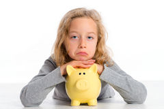 Girl with piggy bank is not happy Stock Image