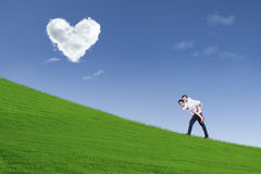 Girl on piggyback ride under heart clouds Royalty Free Stock Image